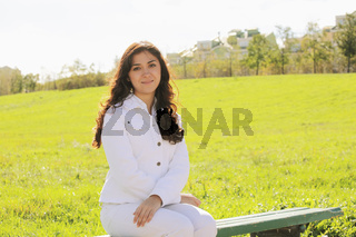 Young brunette sitting on bench