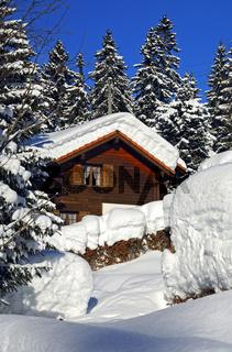 Tiefverschneites Holzhaus