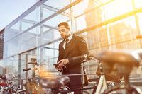 Business Mann sichert Fahrrad mit Smart Lock