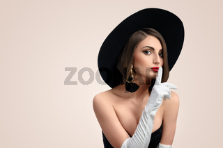 Elegant fashionable woman posing wearing a hat in studio