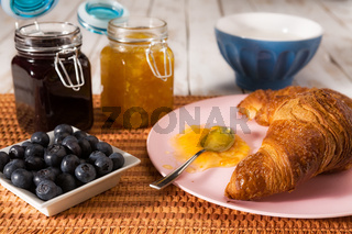 Breakfast with croissant and blueberries over a tablecloth