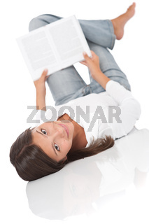 Smiling teenager lying down and reading book