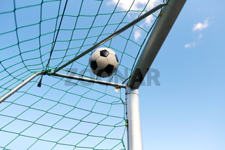 soccer ball flying into football goal net over sky