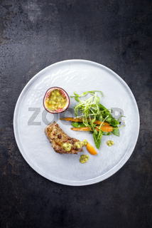 Fried pork tenderloin with vegetable and passion fruit as top view on a plate