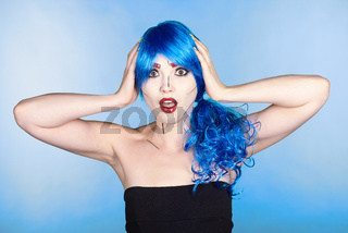Portrait of young woman in comic  pop art make-up style.  Shoked female in blue wig on blue background