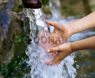 Boy holds hands into a water stream