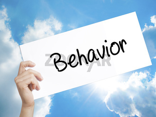 Behavior Sign on white paper. Man Hand Holding Paper with text. Isolated on sky background.