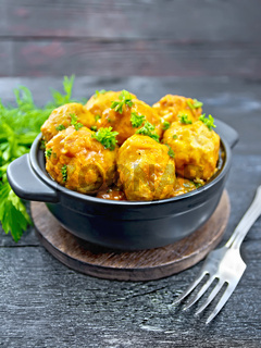 Meatballs in black brazier with greens on board