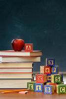 Stack of books with apple and wooden blocks