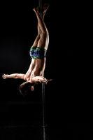 Male pole dance. Guy posing upside down on pylon