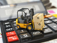 Forklift with cardboxes on calculator. Calculation of shipping delivery costs concept.