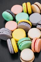 Colorful french macaroons or macarons on black wooden table. Space for text.