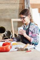 Frau bei der Kaffeepause in Werkstatt