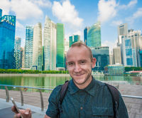 Tourist man taking mobile phone selfie picture at Singapore cityscape