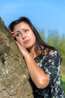 Portrait woman leaning against tree trunk