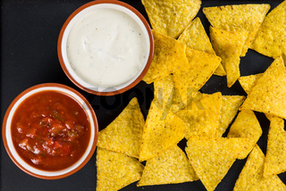 mexican street food nachos  with salsa and cream dip on black background
