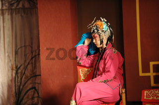 china opera actress sit in a chair