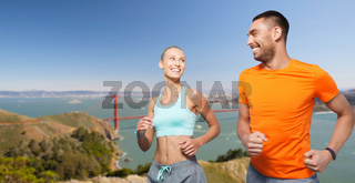 couple running over golden gate bridge background