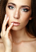 Beauty portrait of young woman touching face with fingers. Brunette girl with long hair and day female makeup