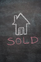 House with sold word on black chalkboard