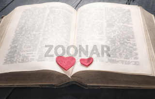 Antique book and two hearts on it