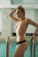 Slim blonde topless in a swimming pool cropped view