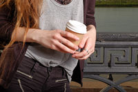 Middle section of ypong woman with takeaway coffee cup in hands instagram effect