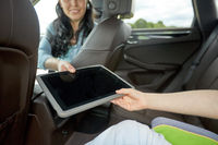 woman giving tablet pc to her child in car