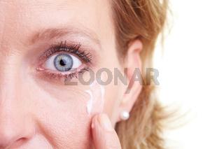Frau cremt Wange ein