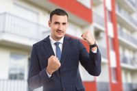 Cheerful joyful realtor or sales man on apartment building background