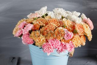 Pink, orange, white carnation flowers in blue bucket on old wood