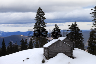 Old wooden hut in winter snow mountains at gray day