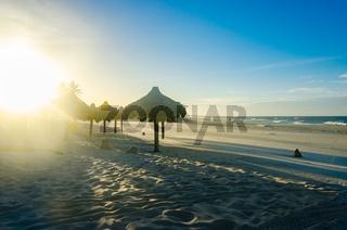 Several beach sun umbrellas at the sunset
