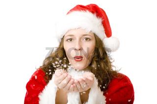 Junge attraktive Frau als Weihnachtskostüm bläst Schnee von den Händen