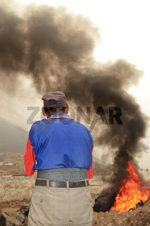 Mann verbrennt Reifen in Slums