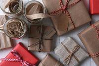 Top view of a group of plain paper wrapped Christmas presents with canning jars filled with string,