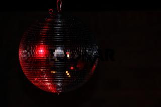 rot reflektierende Diskokugel in der Dunkelheit