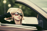 Young fashion woman in sunglasses driving convertible car