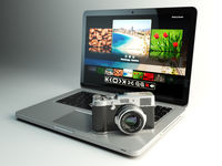 Photo camera and laptop with image viewer on the screen. Digital photography workstation concept.