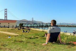 young man enjoying time and famous sightseeing in san francisco - golden gate bridge
