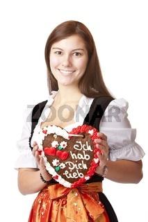 Verliebte junge Frau im Oktoberfest Dirndl hält Lebkuchenherz