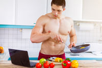 Kochen junger Mann Essen Gemüse Rezept Computer in der Küche gesunde Ernährung