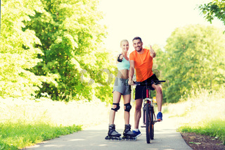 couple on rollerblades and bike showing thumbs up