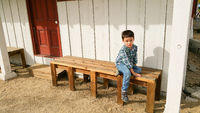 Cute Young Chinese and Caucasian Boy Sitting On Bench Outdoors