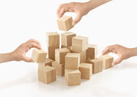 Many hands playing wooden box on isolated background.