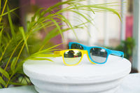 Yellow and blue sunglasses on white terrace dyke over blurred pink house background