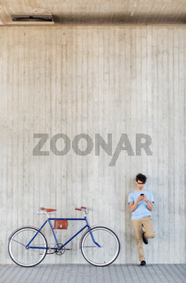 man with smartphone and fixed gear bike on street