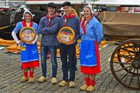 Holländische Käsemädchen und Käsejungen posieren mit einem Gouda Käselaib
