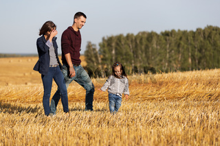 Happy young family with two year old girl walking in a harvested field