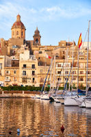 View of Birgu with Our Lady of Annunciation Church over the Dockyard bay with moored yacht. Malta